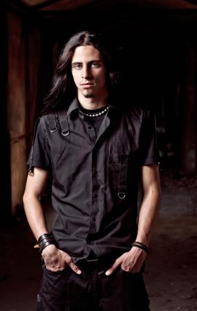 低いキーで長い髪ハンサムな若い男の肖像 写真素材