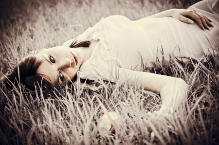 色あせた効果の草の上に横たわる悲しい美しい少女