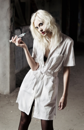 Beautiful young girl in the image of strange mad nurse with syringe in hand  photo