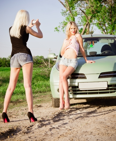 sexy pictures: Two girls shooting near a car Stock Photo