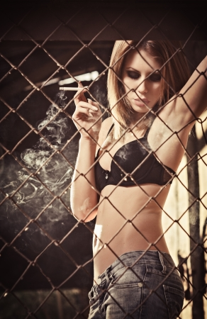 Smoking beautiful young girl stands behind the metallic grid photo