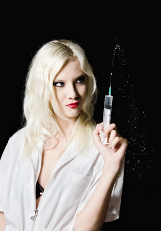 Beautiful young girl in the image of nurse with syringe in hand  Closeup photo