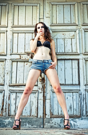 sexy shorts: A sexy girl is standing at the wall and smoking cigarette  Full length