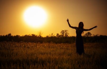 夕焼け空とドレスで踊る少女のシルエット 写真素材