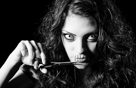 Horror shot  scary strange girl with mouth sewn shut cutting off the thread  Monochrome photo
