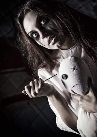 Horror style shot  a scary mad girl with moppet doll and needle in hands