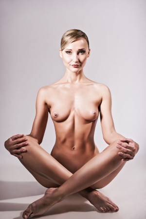 Nude shot of a sexy naked woman sitting in yoga pose photo