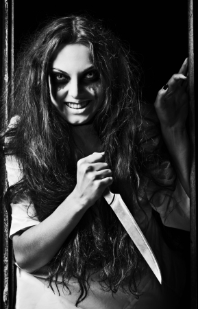 evil girl: Horror style shot  a crazy evil girl with knife in hands  Black and white Stock Photo