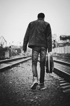 A young man with guitar case in hand is going away  Rear view, black and white Stock Photo