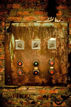 contador electrico: Un viejo panel de control oxidado en la pared de ladrillo