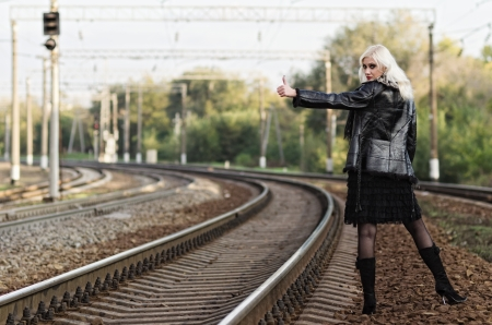 hitchhiking: Beautiful young girl is hitchhiking on a railroad  Rear view Stock Photo