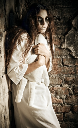 sanitarium: Horror scene  the scared crazy girl with moppet doll in hands Stock Photo