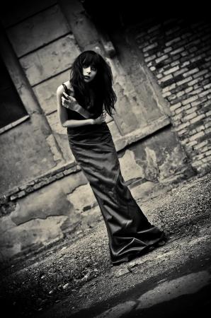 Gloomy portrait of a strange depressive goth girl among the ruins  Low key
