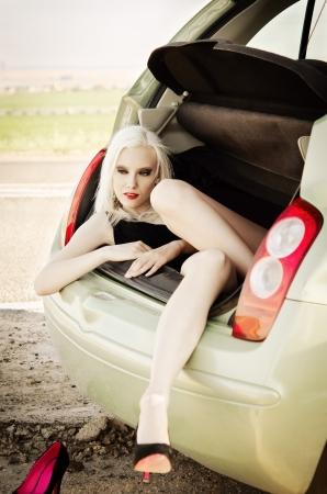 Sexy blonde girl lying in trunk of a car photo