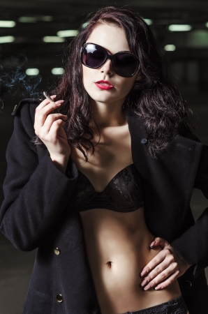 Closeup portrait of beautiful smoking young girl in black underwear and coat photo