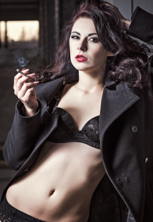 Closeup portrait of sexy smoking vamp woman in black underwear and coat  photo