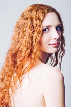 Closeup half-turned portrait of a beautiful smiling redhead girl photo
