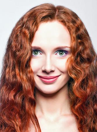 Closeup portrait of a beautiful smiling redhead girl photo