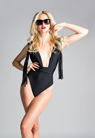 sexy young girl: Studio fashion shot  sexy young girl wearing swimsuit and sunglasses