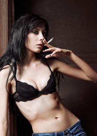 sexy young girl: Sexy young girl smoking a cigarette  Stock Photo
