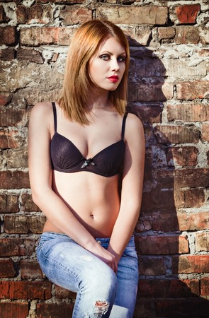 nude outdoors: Beautiful young girl in bra and jeans stands leaning against a brick wall