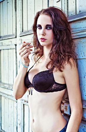 Sexy beautiful young girl smoking a cigarette photo