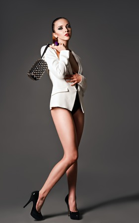 Studio fashion shot  a beautiful girl in white jacket with clutch in hand photo