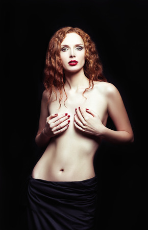 Dramatic studio portrait of a sexy redhead girl photo