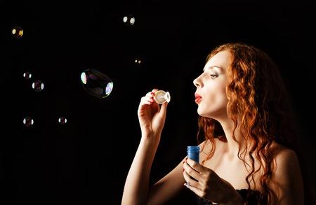 A beautiful redhead girl blows bubbles  Studio portrait, profile view  photo