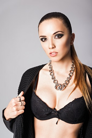 chainlet: Fashion portrait of a pretty young girl wearing black jacket, bra and necklace