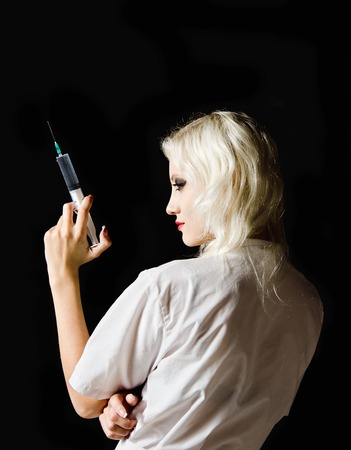 Beautiful young girl in the image of nurse with syringe in hand  Rear view  photo