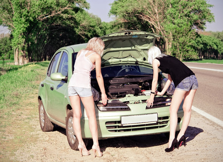 Two blonde girls stand by the broken car and don photo