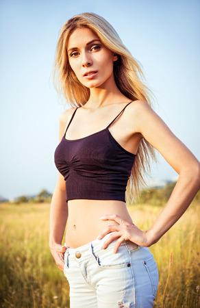 amongst: Portrait of a beautiful young woman amongst the field Stock Photo