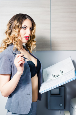 gorgeous businesswoman: A sexy young business woman holds folder and pen