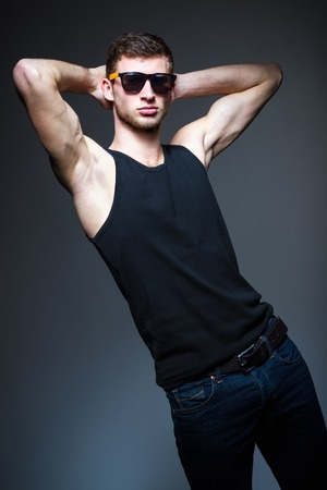 Studio fashion shot  a handsome young man wearing jeans, shirt and sunglasses photo