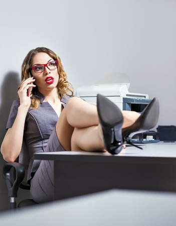 table skirt: A beautiful young business woman talking on the phone