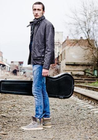 guitar case: Apuesto joven con funda de la guitarra en la mano de pie entre ruinas industriales