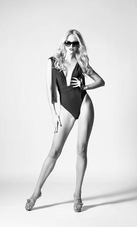 水着とサングラスの黒と白のセクシーな若い女性のスタジオ ファッション撮影