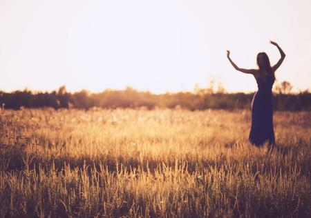 夕焼けの空に踊る女性のぼやけたシルエット