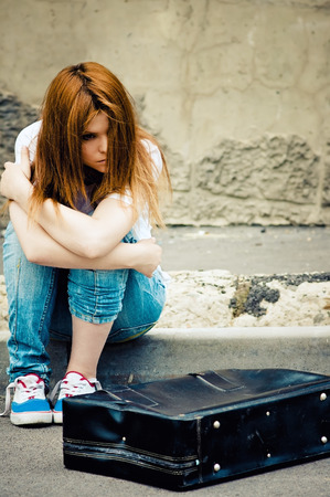 A beautiful young sad girl sitting on asphalt Stock Photo