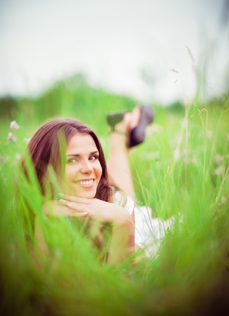 Happy smiling beautiful young woman lying among the grass and flowers photo