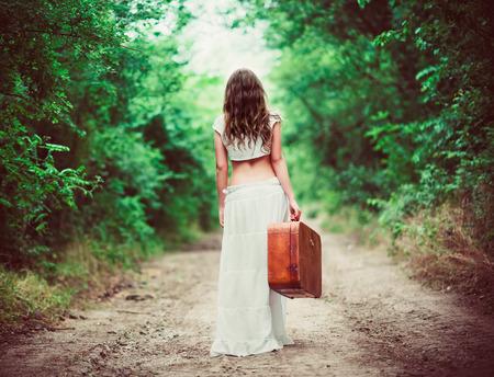 persona cammina: Giovane donna con la valigia in mano andando via da una strada rurale Archivio Fotografico