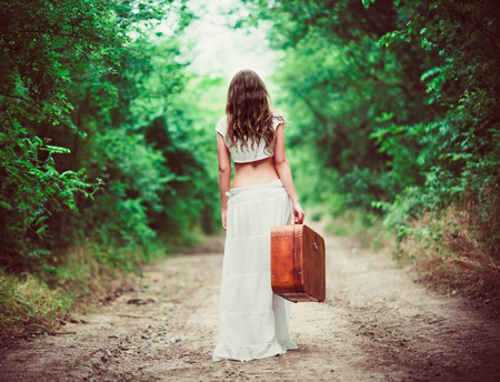 mujer con maleta: Mujer joven con la maleta en la mano va a desaparecer por un camino rural Foto de archivo
