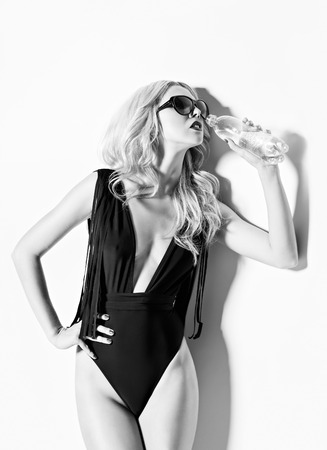 Studio fashion shot  girl in a swimsuit drinking mineral water  Black and white photo
