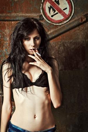 chica fumando: Mujer joven fumar cigarrillos atractiva cerca de la señal de que no haya fuego y fumar Foto de archivo
