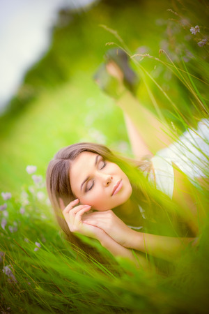 Beautiful young woman sleeping among the grass and flowers photo