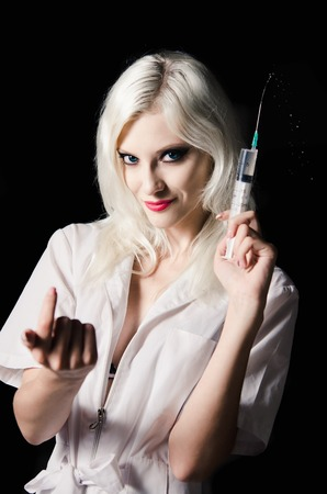Smiling beautiful young woman in the image of nurse with syringe in hand  Closeup