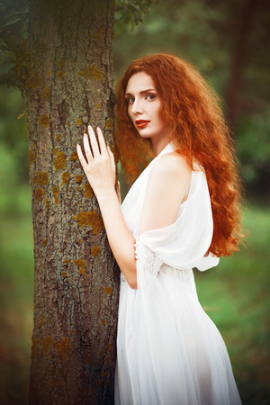 red haired: Beautiful redhead woman wearing white dress stands near the tree