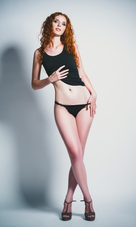 red haired: Studio fashion shot of a sexy young ginger woman in shirt and panties  Full length