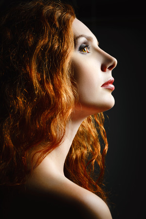 Closeup studio portrait of a beautiful redhead woman  Profile view photo